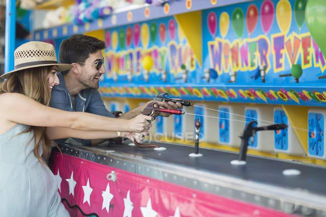 Couple contemporain s'amuser au parc d'attractions jouer eau gicler jeu — Photo de stock