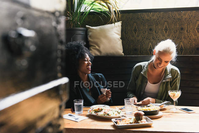 Multicultural smiling friends sharing meal together in cafe — Stock Photo