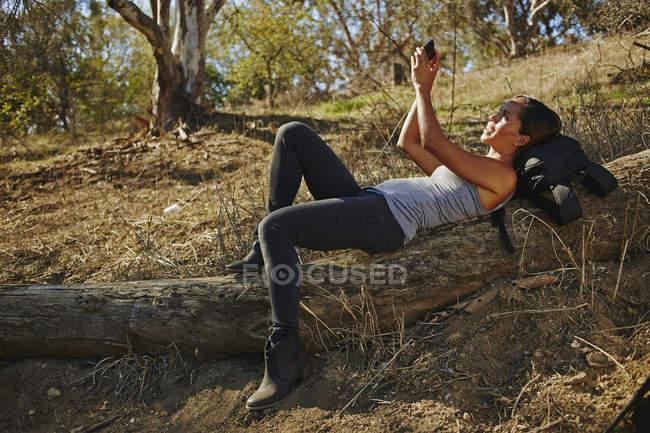 Жінка йде пішки, лежачи на колоді і робить смартфон-сельфі. — стокове фото