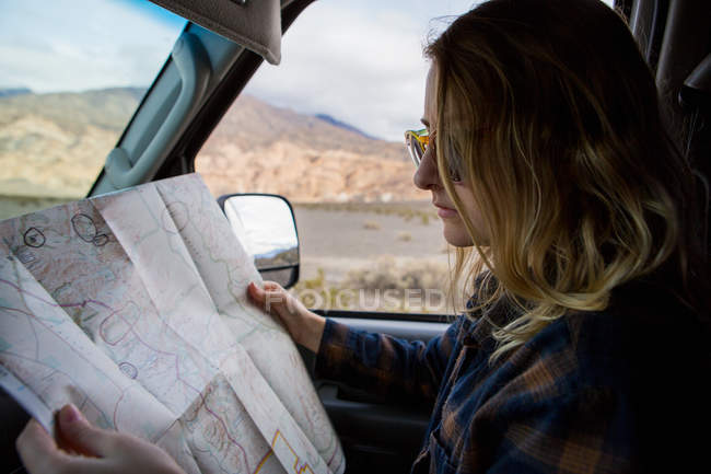 Woman reading map in car, Death Valley National Park, California, US — Stock Photo