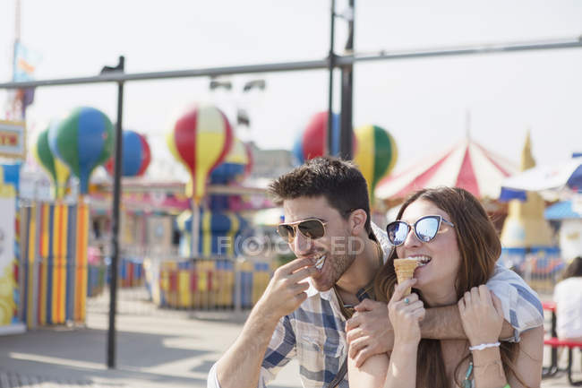 Contemporary couple having a good time on amusement park boardwalk eating soft ice cream — Stock Photo
