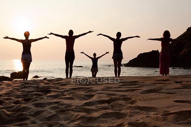 Задний вид женщин, практикующих йогу на пляже на закате — стоковое фото