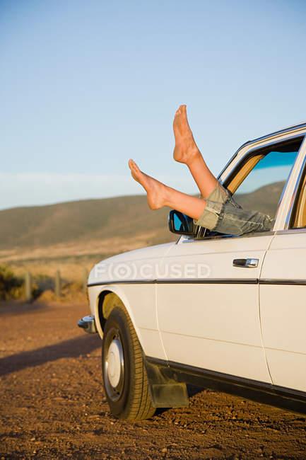 Giovani donne piedi sporgenti da un finestrino di una macchina — Foto stock