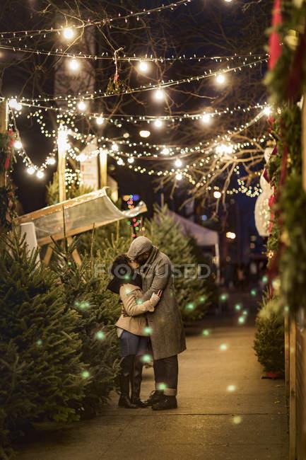 Romantiche coppie felici che godono città durante subacquea vacanze invernali da alberi di Natale — Foto stock