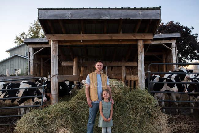 Retrato de pai e filha ao lado de galpão de vaca — Fotografia de Stock