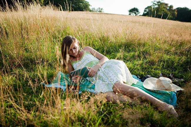 Молодая женщина, лежа на стороне в поле, глядя на ручные устройства — стоковое фото