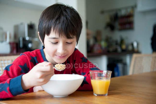 Мальчик ест завтрак Зерновые столом — стоковое фото