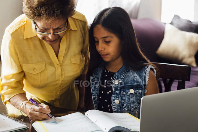Grandmother helping granddaughter with homework — Stock Photo
