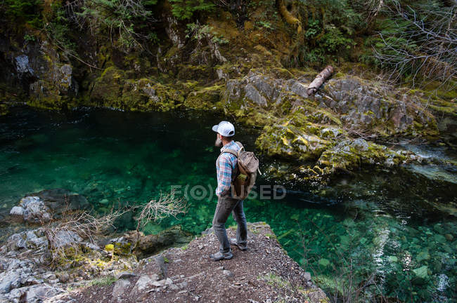 Man standing on rock and looking away at river, Opal Creek, Oregon, EUA — Fotografia de Stock