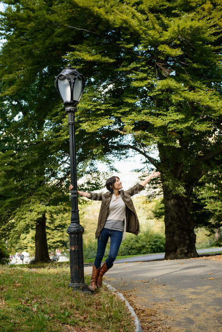 Mulher jogando na luz da rua no parque — Fotografia de Stock