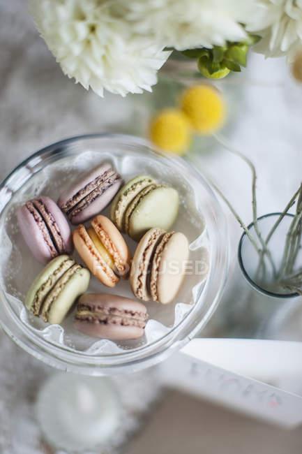 Stillleben mit Macarons in Schüssel mit Blumen in vase — Stockfoto
