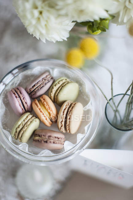 Still life of macarons in bowl with flowers in vase — Stock Photo