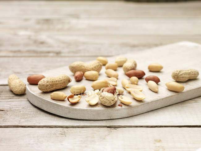 Whole and cracked peanuts on wooden chopping board — Stock Photo