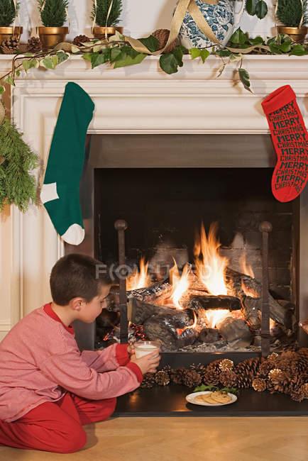 Маленький мальчик, сидя у камина на Рождество — стоковое фото