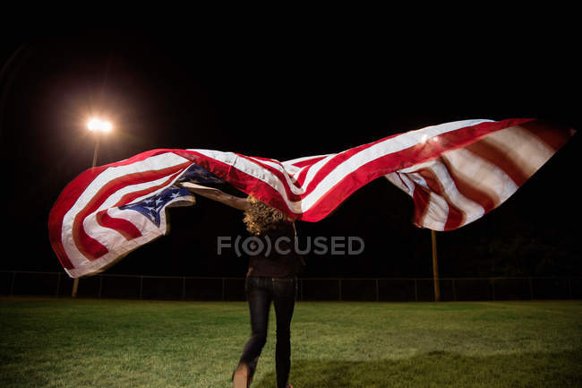 Girl holding american flag at night — Stock Photo