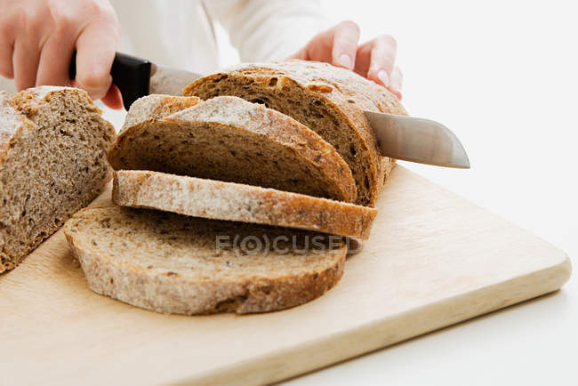 Cropped image of baker slicing loaf of bread isolated on white — Stock Photo