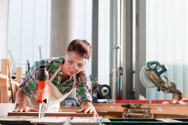 Carpenter using saw in workshop — Stock Photo