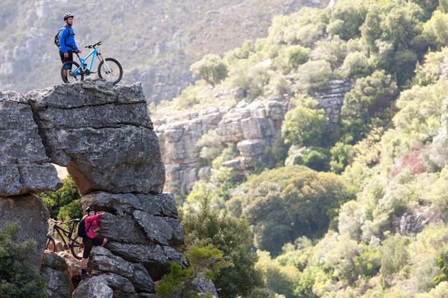Mountain biking couple on rock formation looking ahead — Stock Photo