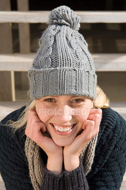 Porträt einer lächelnden jungen Frau mit Strickmütze — Stockfoto