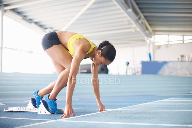Young female athlete on starting blocks — Stock Photo