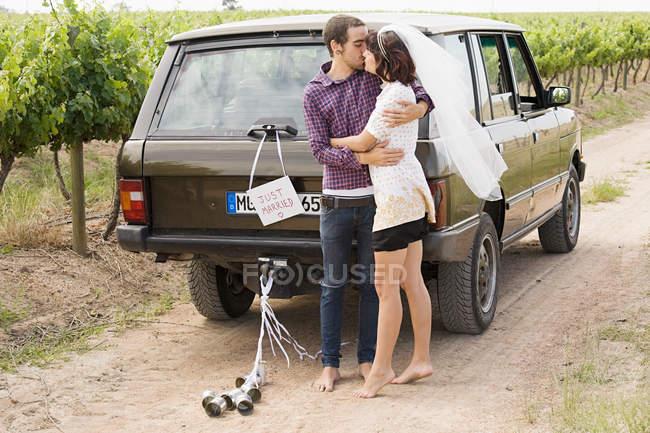 Couple de jeunes mariés s'embrassant par véhicule — Photo de stock