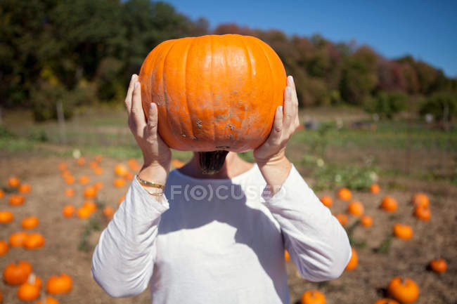 Front view of person holding pumpkin in front of face — Stock Photo