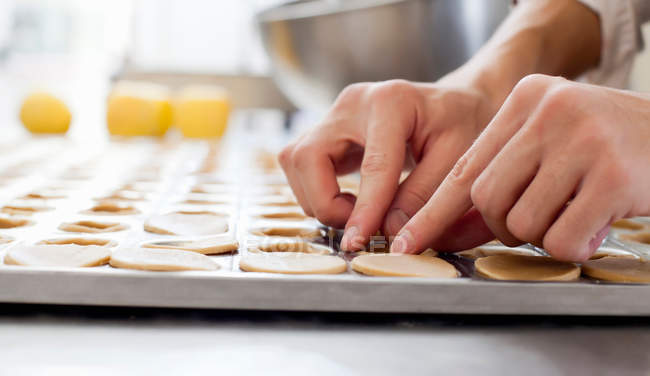 Cropped image of baker shaping pastry in kitchen — Stock Photo