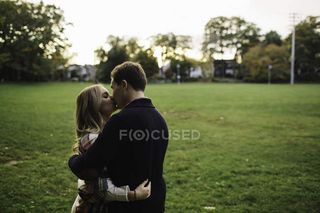 Pareja joven al aire libre, abrazando, besando - foto de stock