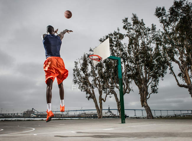 Young basketball player jumping to score — Stock Photo