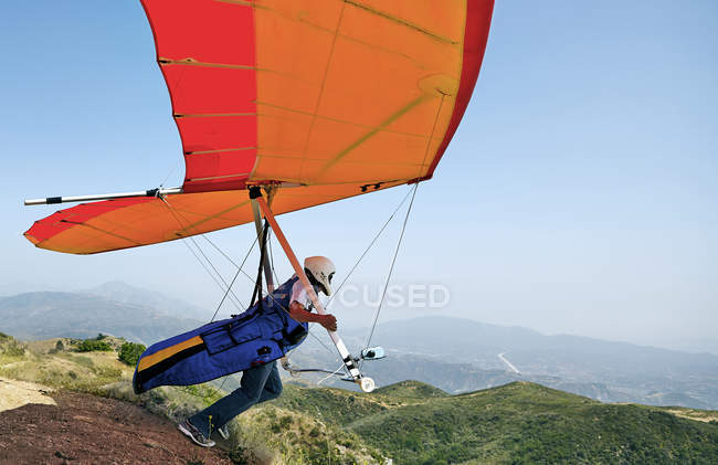 Hang glider pilot taking off — Stock Photo