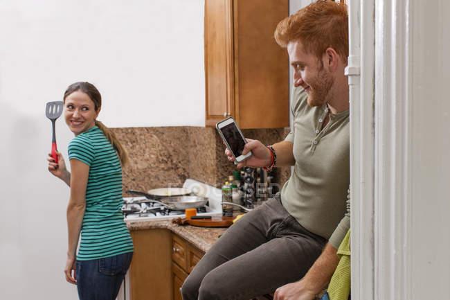 Молодой человек на кухне с помощью смартфона сфотографировать молодой женщины Холдинг шпатель — стоковое фото