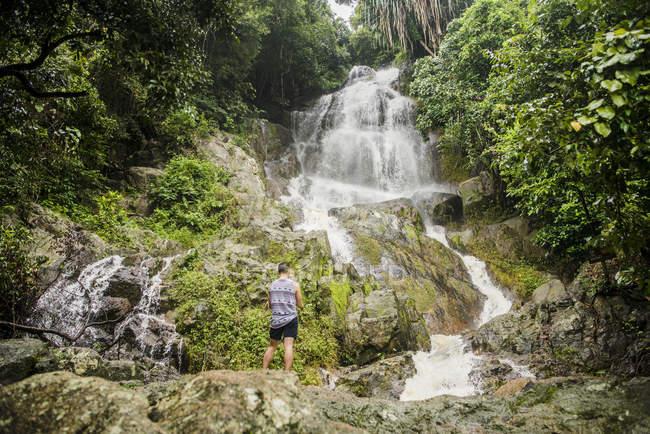 Young man standing on rock looking at Na Muang Waterfall, Koh Samui, Thailand — Stock Photo