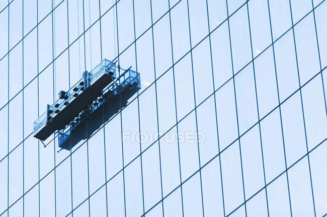 Low angle view of Suspended window cleaning platform on glass building — Stock Photo