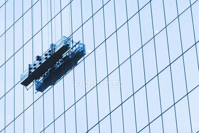 Vista de ángulo bajo de falsos limpiacristales plataforma en edificio de cristal - foto de stock