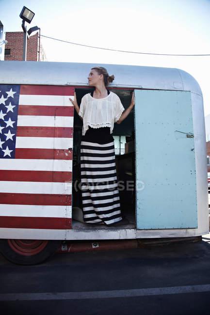 Donna in piedi sulla porta della roulotte con bandiera americana — Foto stock