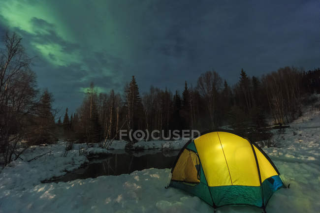 Tent set beside lake under sky illuminated with northern lights — Stock Photo