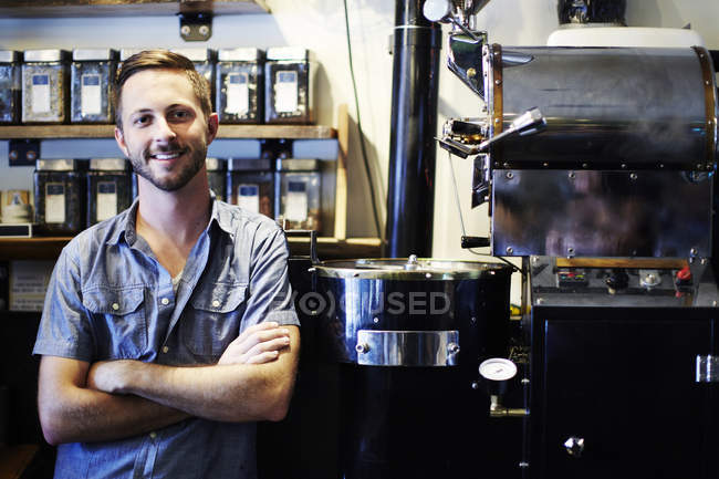 Portrait of young man working in coffee shop — Stock Photo