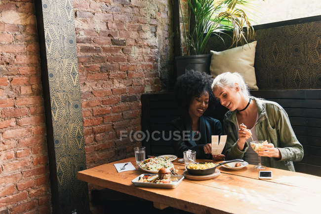 Friends sharing meal together in cafe — Stock Photo