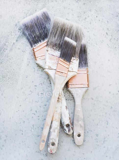 Primo piano colpo di natura morta di pennelli su superficie rustica — Foto stock