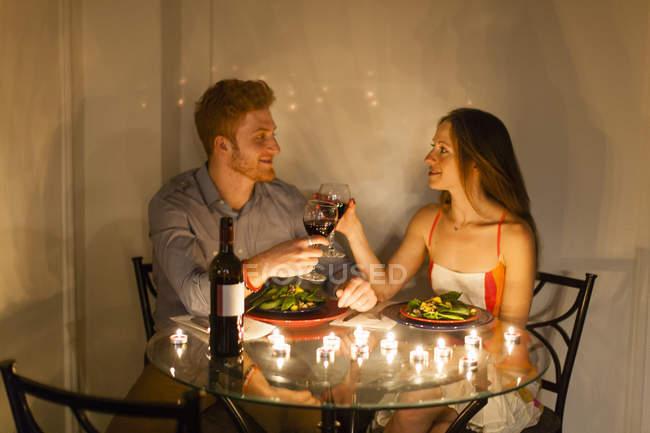 Пара в таблице лицом к лицу пользоваться при свечах, делая тост, улыбаясь — стоковое фото