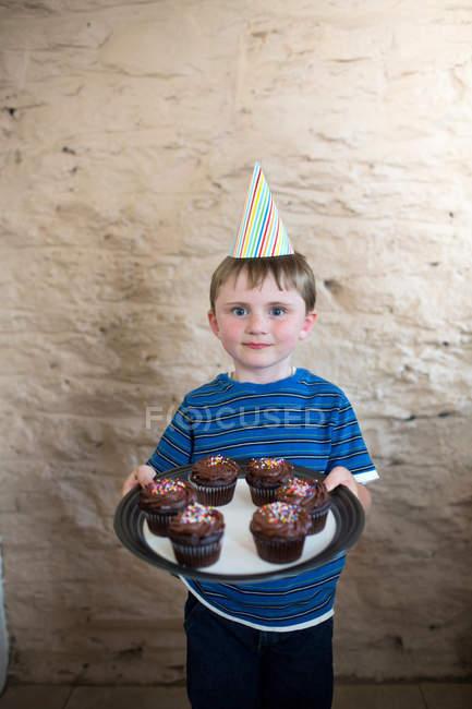 Портрет хлопчик капелюсі партії тримають кекси — стокове фото