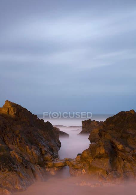 Costa rocosa en la noche - foto de stock