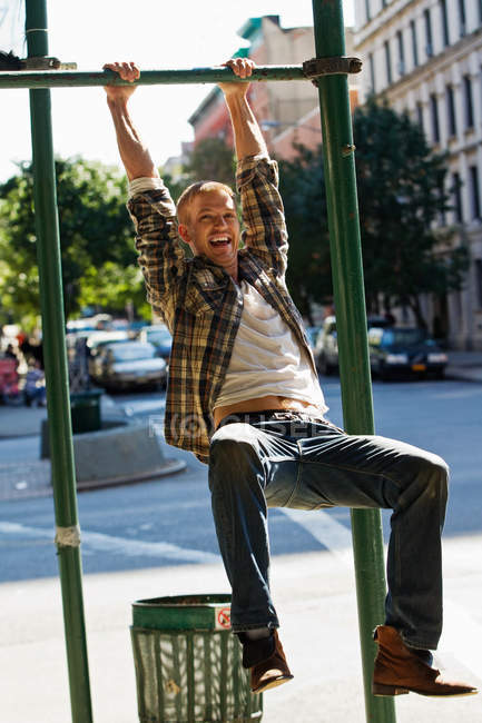 Mid adult man hanging from street lamp post — Stock Photo