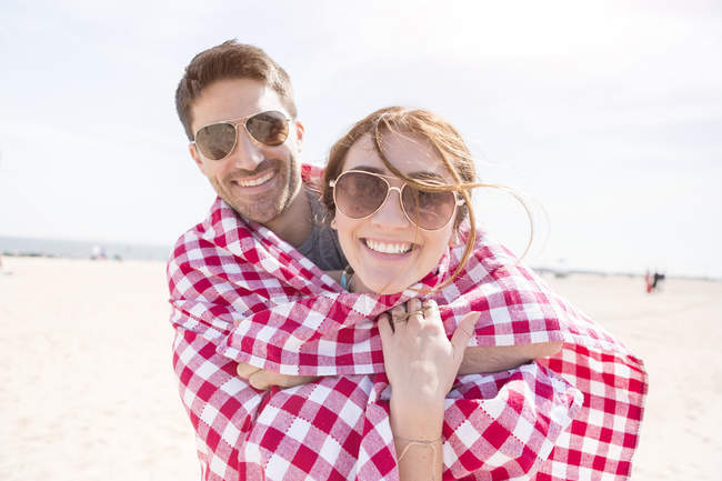 Contemporary couple having a good time on beach wraped in beach blanket — Stock Photo