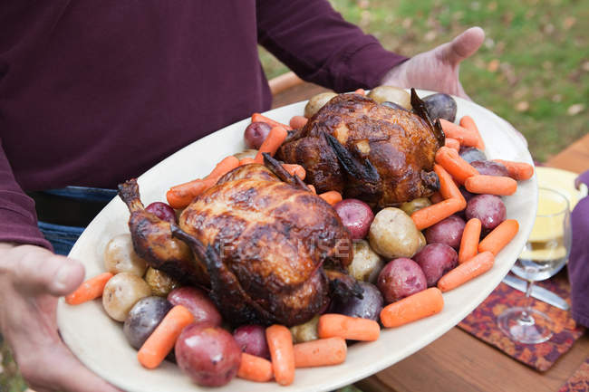 Person holding platter of poultry and vegetables, close-up partial view — Stock Photo
