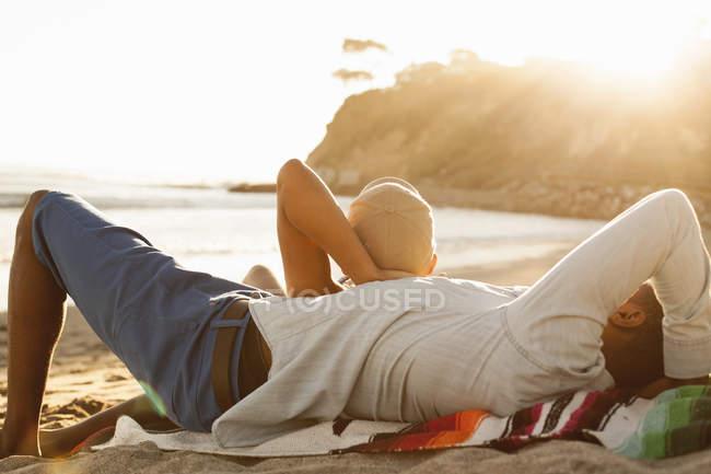 Jeune couple couché ensemble sur la plage, vue arrière — Photo de stock
