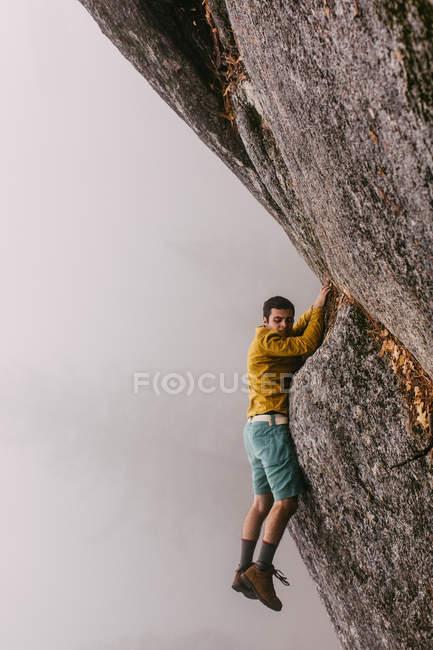 Young man hanging on rock, near Shaver Lake, California, USA — Stock Photo
