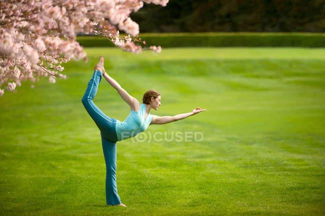Женщина в положении для йоги на носу в парке — стоковое фото