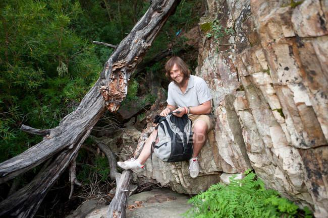 Ritratto di giovane escursionista maschio che fotografa seduto sulla roccia — Foto stock