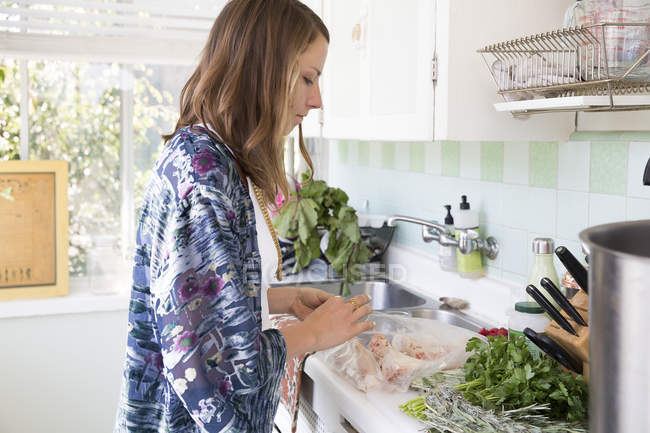 Femme dans la cuisine préparant la nourriture — Photo de stock